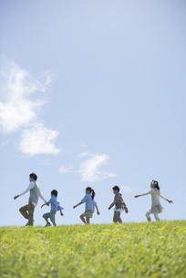 草原を歩く小学生と先生の写真素材 [FYI04549565]