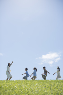 草原を歩く小学生と先生の写真素材 [FYI04549573]