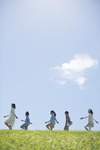 草原を歩く小学生と先生の写真素材 [FYI04549583]