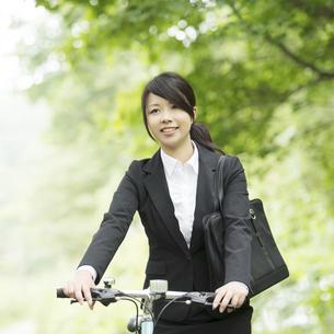 自転車を押すビジネスウーマンの写真素材 [FYI04549627]