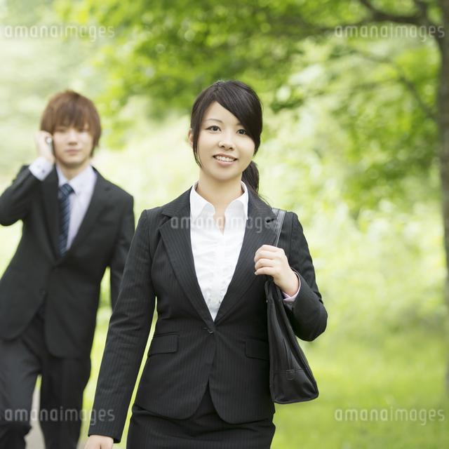 新緑の中で微笑むビジネスウーマンとビジネスマンの写真素材 [FYI04549631]