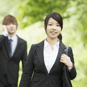 新緑の中で微笑むビジネスウーマンとビジネスマンの写真素材 [FYI04549633]