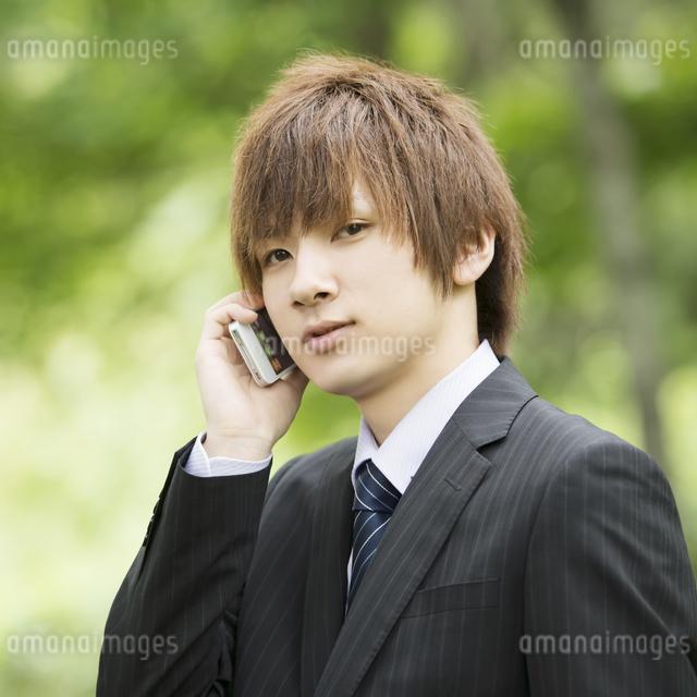スマートフォンで電話をするビジネスマンの写真素材 [FYI04549654]