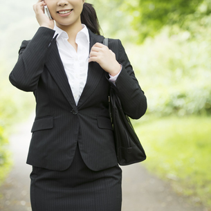 スマートフォンで電話をするビジネスウーマンの写真素材 [FYI04549658]