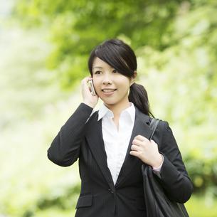 スマートフォンで電話をするビジネスウーマンの写真素材 [FYI04549665]