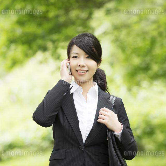 スマートフォンで電話をするビジネスウーマンの写真素材 [FYI04549666]