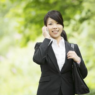 スマートフォンで電話をするビジネスウーマンの写真素材 [FYI04549668]