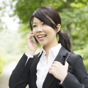 スマートフォンで電話をするビジネスウーマンの写真素材 [FYI04549671]