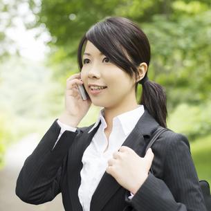 スマートフォンで電話をするビジネスウーマンの写真素材 [FYI04549672]