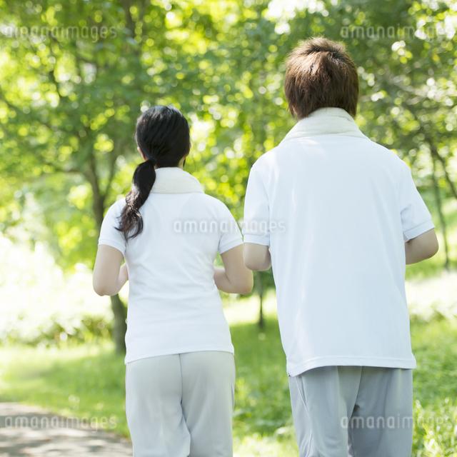 ジョギングをするカップルの後姿の写真素材 [FYI04549799]