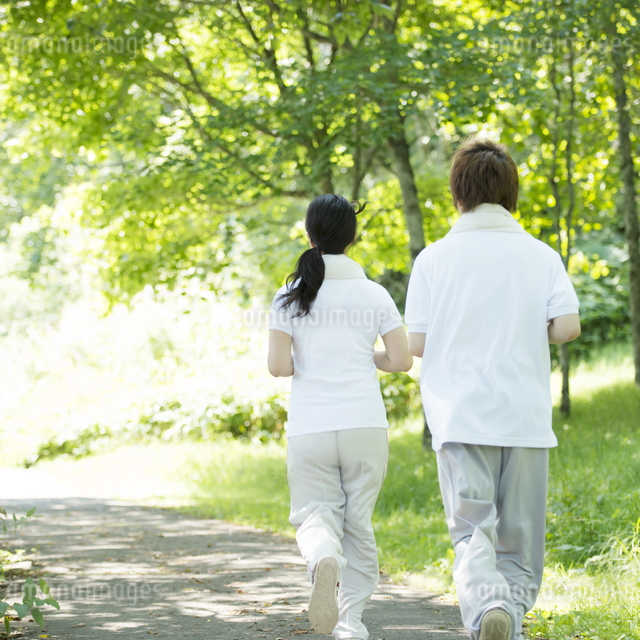 ジョギングをするカップルの後姿の写真素材 [FYI04549800]