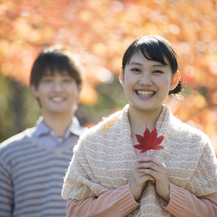 紅葉の前で微笑むカップルの写真素材 [FYI04549848]