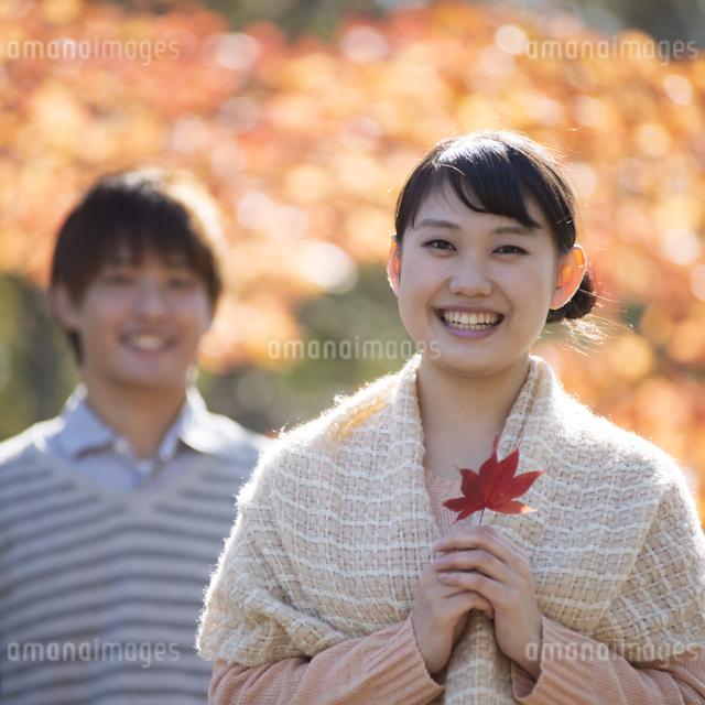 紅葉の前で微笑むカップルの写真素材 [FYI04549849]