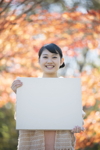 紅葉の前でメッセージボードを持ち微笑む女性の写真素材 [FYI04549925]