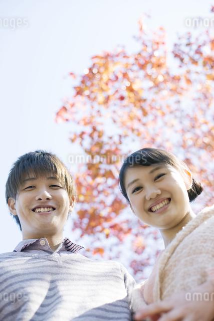 紅葉の前で微笑むカップルの写真素材 [FYI04549978]