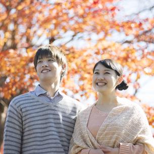 紅葉の前で微笑むカップルの写真素材 [FYI04549997]