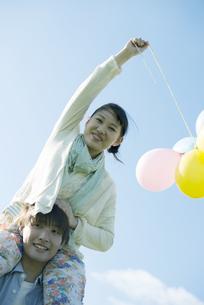風船を持ち肩車をするカップルの写真素材 [FYI04550029]