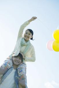 風船を持ち肩車をするカップルの写真素材 [FYI04550030]