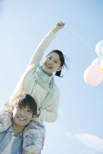 風船を持ち肩車をするカップルの写真素材 [FYI04550032]