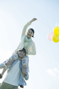 風船を持ち肩車をするカップルの写真素材 [FYI04550035]