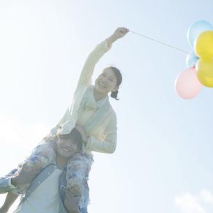 風船を持ち肩車をするカップルの写真素材 [FYI04550037]
