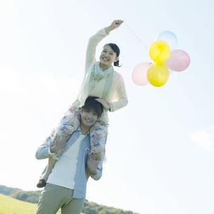 風船を持ち肩車をするカップルの写真素材 [FYI04550039]