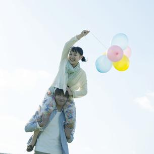 風船を持ち肩車をするカップルの写真素材 [FYI04550040]