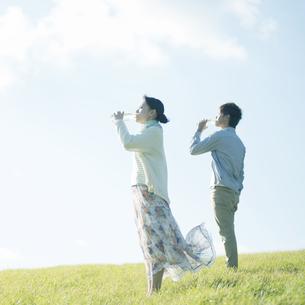 草原で水を飲むカップルの写真素材 [FYI04550057]