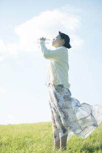 草原で水を飲む女性の写真素材 [FYI04550059]