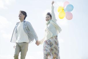 風船を持ち走るカップルの写真素材 [FYI04550065]