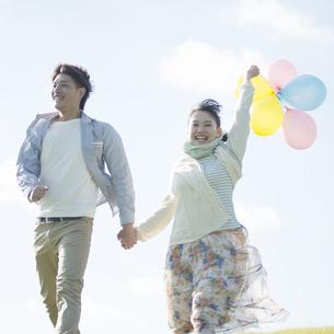 風船を持ち草原を走るカップルの写真素材 [FYI04550066]