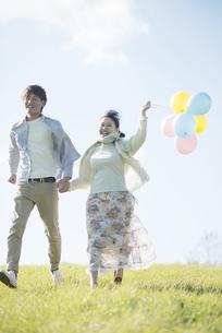 風船を持ち草原を走るカップルの写真素材 [FYI04550076]
