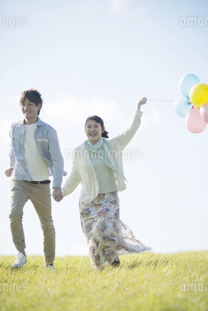 風船を持ち草原を走るカップルの写真素材 [FYI04550078]