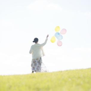 風船を持ち草原を走る女性の後姿の写真素材 [FYI04550087]