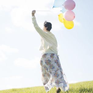 風船を持ち草原を走る女性の後姿の写真素材 [FYI04550096]