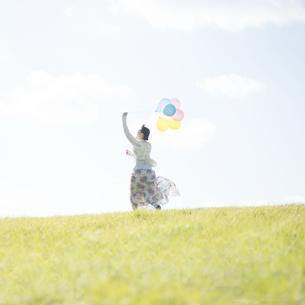風船を持ち草原を走る女性の後姿の写真素材 [FYI04550098]