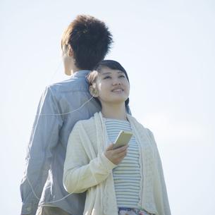 スマートフォンで音楽を聴くカップルの写真素材 [FYI04550106]