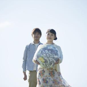 地球のボールを持ち微笑むカップルの写真素材 [FYI04550127]