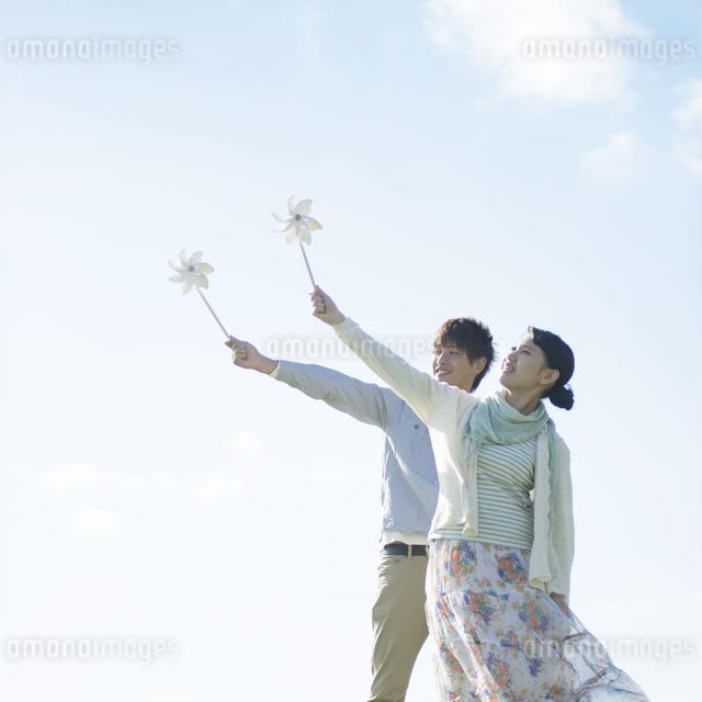 風車を持ち微笑むカップルの写真素材 [FYI04550147]
