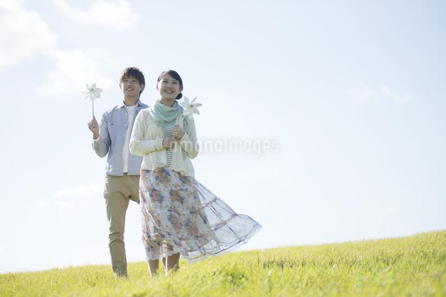 風車を持ち微笑むカップルの写真素材 [FYI04550159]