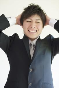 頭を抱えるビジネスマンの写真素材 [FYI04550181]