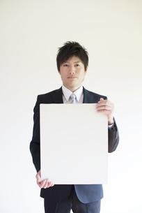メッセージボードを持つビジネスマンの写真素材 [FYI04550196]