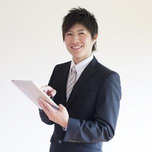 タブレットPCを操作するビジネスマンの写真素材 [FYI04550205]