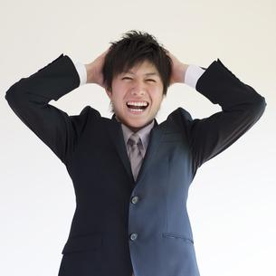 頭を抱えるビジネスマンの写真素材 [FYI04550216]