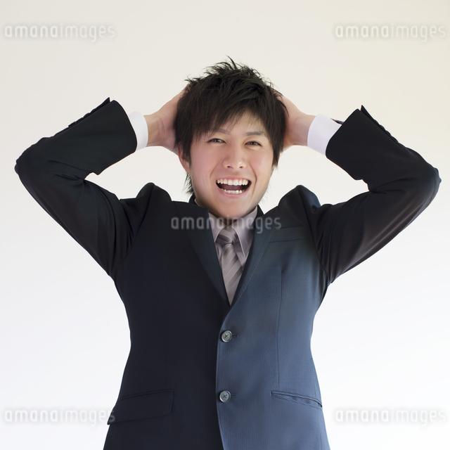 頭を抱えるビジネスマンの写真素材 [FYI04550217]