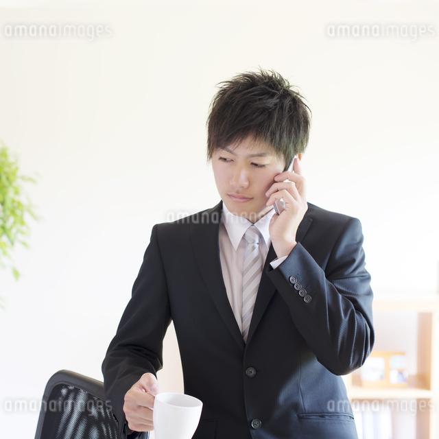 スマートフォンで電話をするビジネスマンの写真素材 [FYI04550271]
