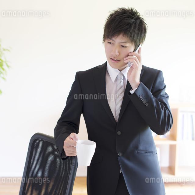 スマートフォンで電話をするビジネスマンの写真素材 [FYI04550273]