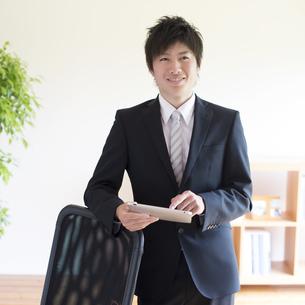 タブレットPCを持ち微笑むビジネスマンの写真素材 [FYI04550276]