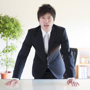 机に手をつくビジネスマンの写真素材 [FYI04550293]