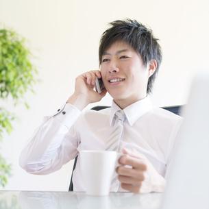 スマートフォンで電話をするビジネスマンの写真素材 [FYI04550328]